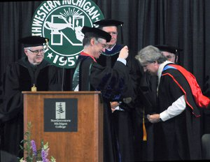 NMC Vice President Stephen Siciliano gives a faculty excellence award to astronomy instructor Jerry Dobek at NMC's 2015 Commencement.