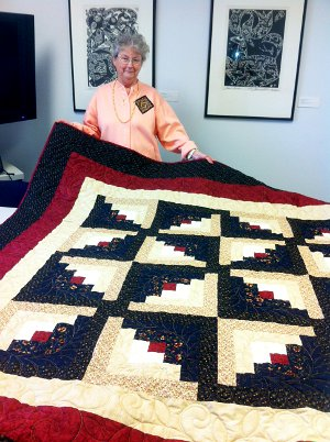 "The ""Windmill"" Log Cabin Quilt, made by Bonnie King (pictured) and quilted by Barb Gurn."