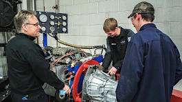 Wayne Moody and students working on a car transmission