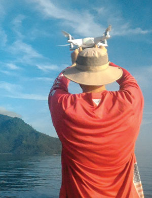 Ryan Mater prepares to launch an NMC drone in Indonesia's Bunaken National Park